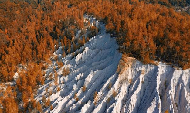 Stare sztuczne wzgórze z odsiewania gruzu w jesiennym lesie.