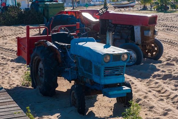 Stare traktory stojące na plaży.