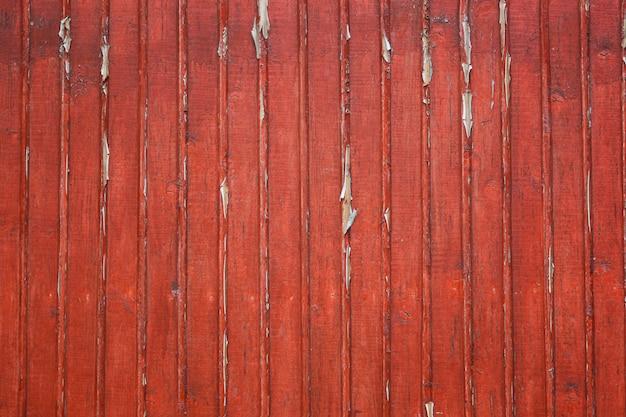 Stare wytarte drewniane deski z czerwoną krakingową farbą jako tło.
