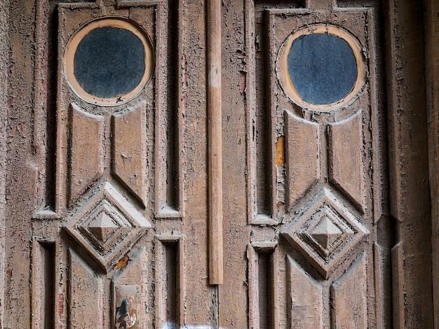 Stare zabytkowe drewniane drzwi z dwoma okrągłymi oknami i wzorami