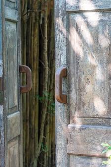 Stare zabytkowe drewniane drzwi z uchwytem w tropikalnym ogrodzie, wyspa koh phangan, tajlandia. ścieśniać