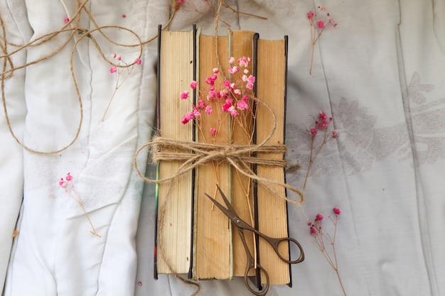 Stare zabytkowe książki i piękne kwiaty na białym tle
