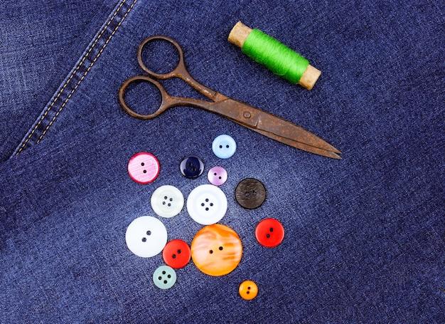Stare zabytkowe nożyczki, guziki i zielone nitki leżą na stylowym denimowym tle