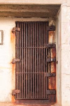 Stare zardzewiałe drzwi w postaci grubej metalowej kraty