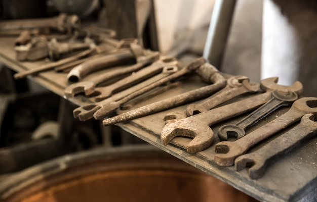 Stare zardzewiałe klucze i narzędzia na półce, nikt. rdza metalu, brudne klucze, korozja, nieczysty sprzęt