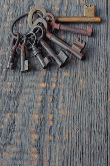 Stare zardzewiałe klucze na metalowym kółku leżą na drewnianym stole