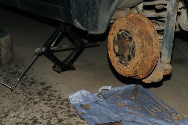 Stare zardzewiałe tylne hamulce samochodu. maszyna zostaje podniesiona na podnośniku, naprawa, wymiana awarii.