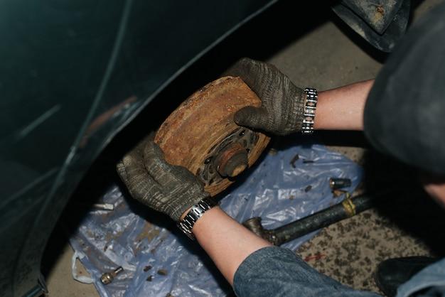 Stare zardzewiałe tylne hamulce samochodu. zbliżenie pracownika naprawiającego wadliwą część w samochodzie, nierozpoznawalna osoba