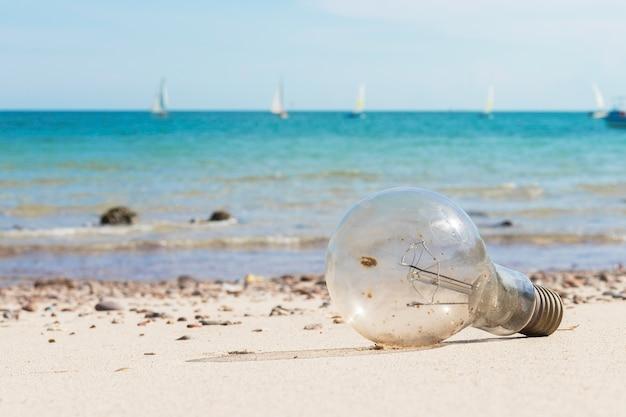Stare żarówki na plaży i niebieski ocean.