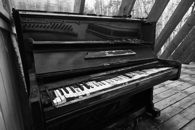 Stare zepsute zabytkowe pianino czarne zniszczone i zapomniane pianino w opuszczonym miejscu czarno-białe