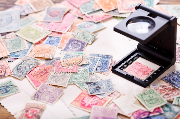 Stare znaczki pocztowe z różnych krajów i szkło powiększające na drewnianym stole