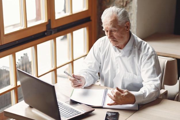 Starego człowieka obsiadanie przy stołem i działanie z laptopem