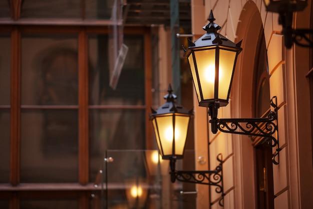 Staromodna latarnia uliczna w nocy. jasno oświetlone latarnie uliczne o zachodzie słońca. lampy ozdobne. magiczna lampa o ciepłym żółtym świetle w miejskim zmierzchu