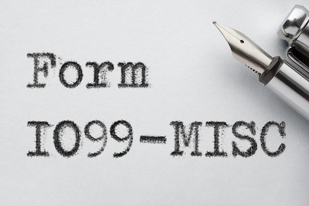Staromodne stalowe pióro wieczne ze słowami form 1099-mics wydrukowanymi na maszynie do pisania