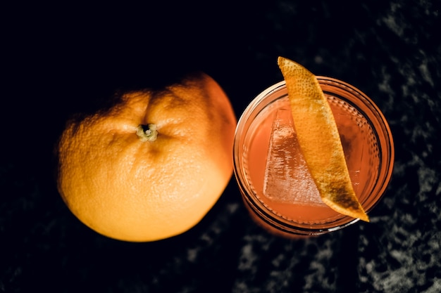 Staromodny koktajl ze skórką pomarańczy w pięknych kieliszkach na ciemnej powierzchni. widok z góry