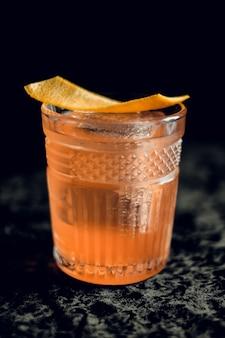 Staromodny koktajl ze skórką pomarańczy w pięknych kieliszkach na ciemnej powierzchni