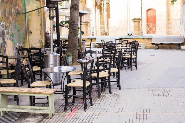 Staromodny taras kawiarni ze stołami i krzesłami.