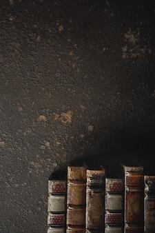Staroświeckie mieszkanie leżało ze stosem starych, oprawionych w skórę książek na tle ciemnej ściany. literatura, czytanie, koncepcja edukacji. styl retro, vintage. miejsce na reklamę. archiwum antyczne.