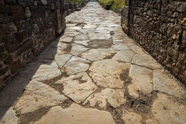 Starożytna droga rzymska. ulica w rzymskich ruinach baelo claudia, położona w pobliżu tarify. andaluzja. hiszpania.