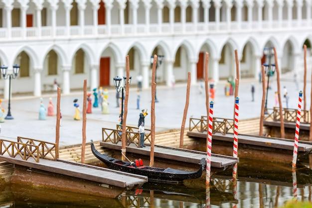 Starożytna łódź na molo, ludzie chodzą po brzegu