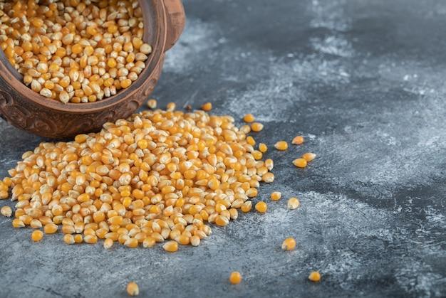 Starożytna miska pełna niegotowanych nasion popcornu.