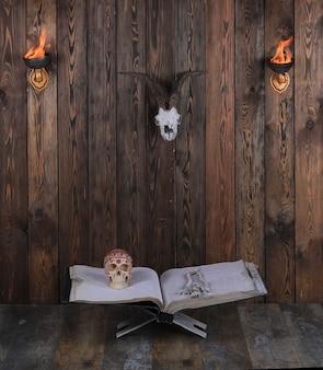 Starożytna otwarta księga z czaszką na drewnianym tle