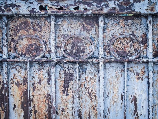 Starożytna rdza drzwi, porysowana niebieska farba i rdza.
