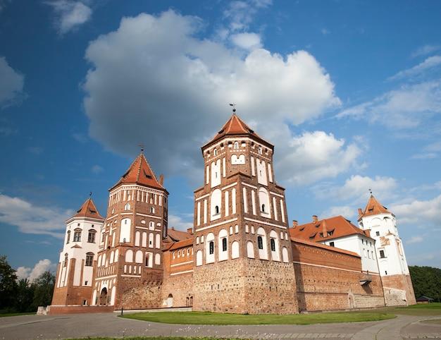 Starożytna twierdza znajdująca się w mieście mir na białorusi. zdjęcie z bliska, na powierzchni błękitnego nieba z chmurami