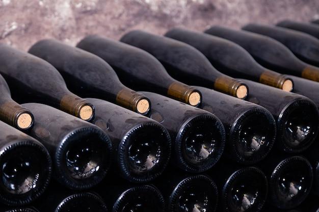 Starożytne ciemne zakurzone butelki wina starzejące się w podziemnej piwnicy w rzędach. koncepcja winiarni z rzadkimi winami, ekskluzywna kolekcja. stosy butelek wina odpoczywają, leżą płasko w stojakach w starej jaskini