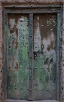 Starożytne drzwi z rycinami przedstawiającymi starożytny dom z błota w omanie