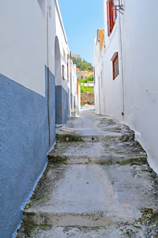 Starożytne greckie miasto lindos. widok z podnóża akropolu. wąska ulica miasta lindos