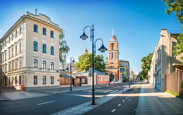 Starożytne i nowoczesne budynki oraz kościół świętej trójcy przy ulicy pyatnitskaya w moskwie w wczesny słoneczny letni poranek