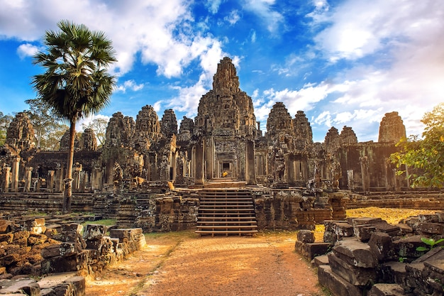 Starożytne kamienne twarze o zachodzie słońca świątyni bayon, angkor wat, siam reap, kambodża.