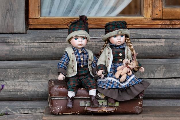 Starożytne porcelanowe lalki siedzą na walizce w pobliżu domu z bali.