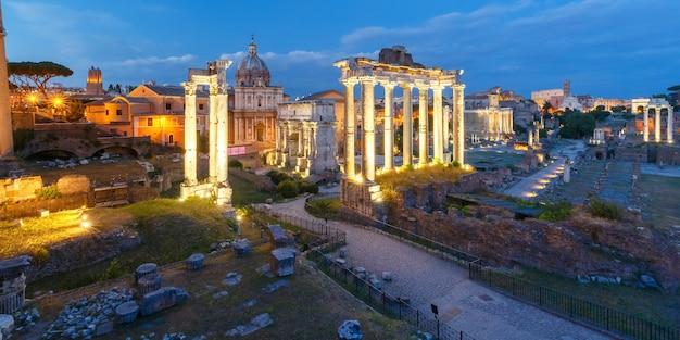 Starożytne ruiny forum romanum lub foro romano podczas wieczornej niebieskiej godziny w rzymie, włochy. panoramiczny widok z kapitolu