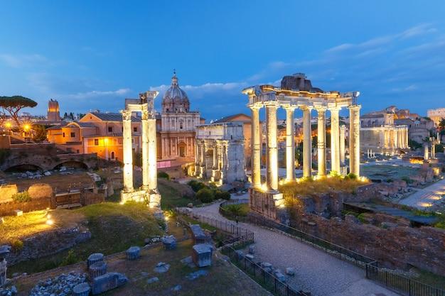Starożytne ruiny forum romanum lub foro romano podczas wieczornej niebieskiej godziny w rzymie, włochy. widok ze wzgórza kapitolińskiego