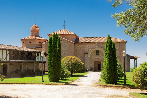Starożytne sanktuarium z cyprysami i starym domem.