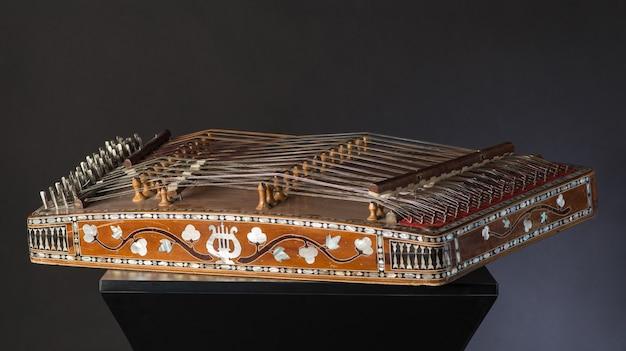 Starożytny azjatycki strunowy instrument muzyczny na czarnym tle podobieństwo harfy i psałterium