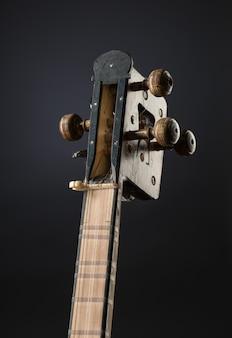 Starożytny azjatycki strunowy instrument muzyczny na czarnym tle z podświetleniem. kołek do strojenia