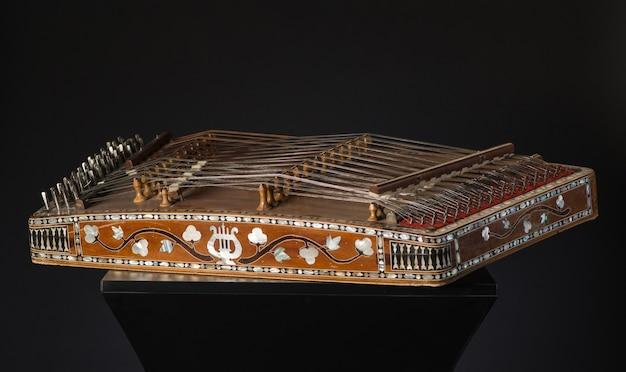 Starożytny azjatycki strunowy instrument muzyczny na czarnym tle z podświetleniem