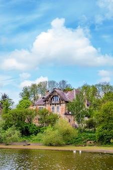 Starożytny budynek w stylu gotyckim nad brzegiem rzeki pod błękitnym niebem z białymi chmurami
