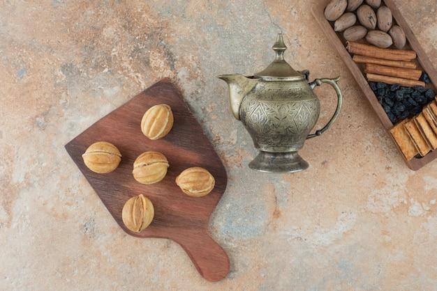 Starożytny czajnik i słodkie okrągłe ciasteczka na tle marmuru
