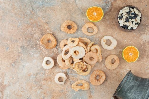 Starożytny imbryk pełen suszonych jabłek z pół pokrojoną mandarynką