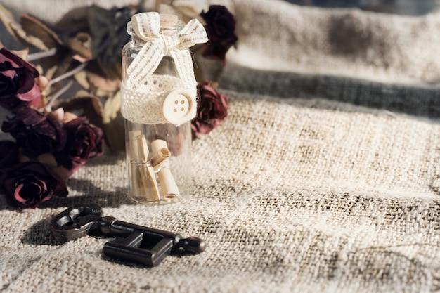 Starożytny klucz i przewiń wiadomość w butelce z białym płótnie. koncepcja na walentynki