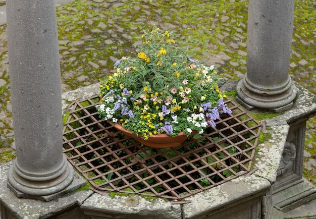 Starożytny krużganek z kamienia w centrum ogrodu klasztornego we włoszech.