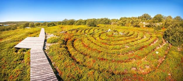 Starożytny labirynt kamieni i trawy na wyspie zayatsky oraz drewniane chodniki dla turystów