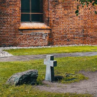 Starożytny nagrobek z kamiennym krzyżem jest nieznany nikomu w pobliżu ceglanego muru zamku. wygaszacz ekranu w tle dla raportów tematycznych.