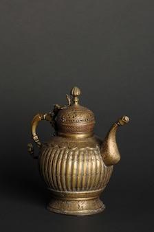 Starożytny orientalny czajniczek metalowy na ciemnym tle. antyczne naczynia z brązu