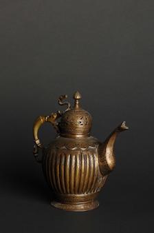 Starożytny orientalny czajnik metalowy na ciemnym tle. antyczne naczynia z brązu