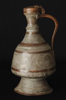 Starożytny orientalny dzbanek metalowy na ciemnym tle. antyczne naczynia z brązu